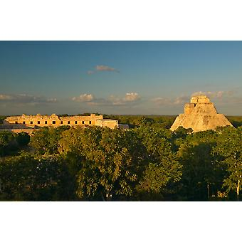 A panoramic view from left to right Nunnery Quadrangle and the Pyramid of the Magician Mayan ruin of Uxmal at sunset in the Yucatan Peninsula Mexico Poster Print by Panoramic Images (36 x 24)