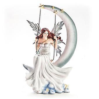 Vita Fairy statyett sitter på månen gunga