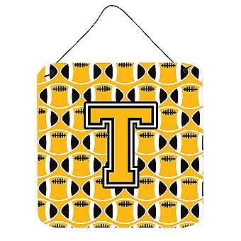يطبع الحرف T الأسود لكرة القدم، والذهب القديم والجدار الأبيض أو الباب معلقة