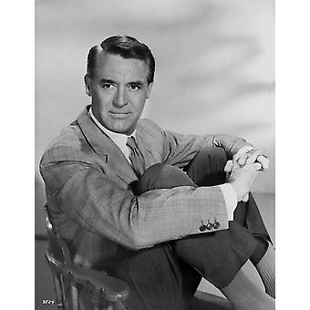 Cary Grant in a blazer and tie sitting down with arms around legs - Photo Print